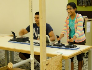 Camp participant tries her hand driving the Raider Robotix competition robot.
